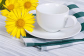White cup and saucer with bouquet of daisies on a wooden table — Stock Photo