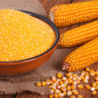 Corn groats in a bowl, whole grain and cob on a wooden table. - Stock Photo