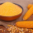 Corn groats in a bowl, whole grain and cob on a wooden table. — Stock Photo
