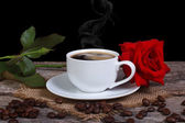 Hot black coffee and red rose on a wooden table. low key — Stock Photo