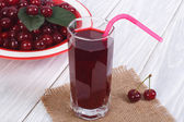 Glass of cherry juice and plenty of ripe cherries on the table — Stock Photo