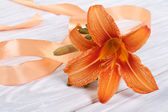 Lily flower with orange ribbon on a wooden table — Stock Photo