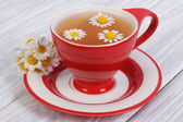 Herbal tea with chamomile flowers in a red cup — Stock Photo