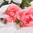Stock Photo: Pink roses with white ribbon on wooden table