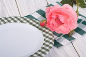 Table setting. beautiful pink rose and a plate on the table — Stock Photo