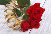 Red roses with gold ribbon on background wooden table — Stock Photo