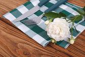 Příbor nůž a vidličku a bílou růži na ubrousek — Stock fotografie