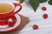 Tea with raspberries in a red cup on the table — Stock Photo