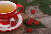 Tea with raspberries in a red cup on old wooden table — Stock Photo
