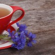 Herbal tea and a bouquet of cornflowers on the old board — Stock Photo