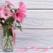 Lavatera pink flowers in a glass vase against a wooden wall — Stock Photo #30039735