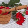 Mortar with rose petals and a red flower buds — Stock Photo