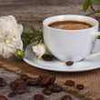 Black coffee on the table and a white rose flower — Stock Photo