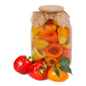 Canned and fresh pepper in a glass jar isolated on white — Stock Photo