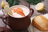Creamy soup with shrimp and lemon in a pot on the table — Stock Photo