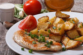 Fried potatoes with chicken steak and vegetables — Stock Photo