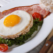 Stock Photo: Fried eggs with bacon and vegetables and rice bread.