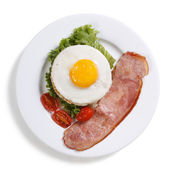 Fried eggs with vegetables and ham isolated. top view. — Stock Photo