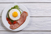 Fried egg with ham and cherry tomatoes on a table. — Stock Photo