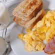 Stock Photo: Scrambled eggs with bacon, toast and milk for breakfast