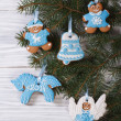 Gingerbread figures on the Christmas tree on a wooden background — Stock Photo