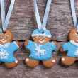 Three blue gingerbread men. Girl with bow and two boys — Stock Photo #36003095