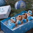 Gingerbread men in blue gift box on the background of Christmas balls and tree — Stock Photo #36004435