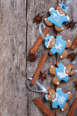 Funny gingerbread men with cinnamon on wooden background — Stock Photo