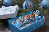 Gingerbread men in blue gift box on the background of Christmas balls and tree — Stock Photo