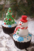 Cupcake Christmas snowman on the background of fir trees — Stock Photo