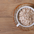Dry oat flakes on a plate top view — Stock Photo