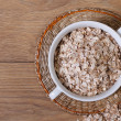 Oat flakes in a bowl and scattered on the table. top view — Stock Photo