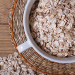 Oat flakes in a bowl and scattered. View from above. close-up — Stock Photo