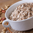 Oat flakes in a bowl and scattered on the table nuts. close-up — Стоковая фотография