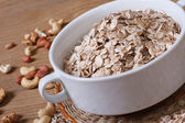 Oat flakes in a bowl and scattered on the table nuts. close-up — Stock Photo