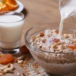 Jet milk pouring onto cereal with dried fruits — Stock Photo #36620417