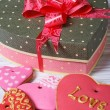 Box with a bow and multicolored cookies hearts on the table.  — Stock Photo