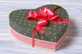 Pink box with green cover in the form of heart with a bow — Stock Photo