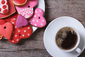 Black coffee and colorful heart cookies on a wooden table — Stockfoto