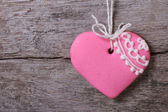 Pink heart with a pattern on a background of wooden board. — Stock Photo