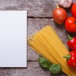 Stock Photo: Spaghetti, vegetables and spices and a notepad on the old table