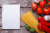 Spaghetti, vegetables and spices and a notepad on the old table — Stock Photo