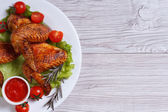 Fried chicken wings with sauce and vegetables top view — Stock Photo