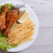 Two fried chicken drumsticks with french fries. top view — Stock Photo #38552171