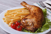 Portion of French fries with chicken leg close-up — Stockfoto