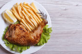 Portion of chicken legs, french fries on a white plate. — Stock Photo