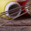 Sewing needles close-up on a background of spools of thread. — Stock Photo
