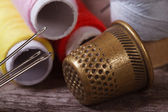 Thimble and needles for sewing closeup on a background thread — Stock Photo