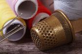 Dedal y agujas para coser closeup en un subproceso de fondo — Foto de Stock