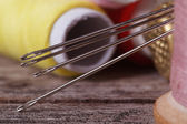 Sewing needles close-up on a background of spools of thread. — Foto Stock